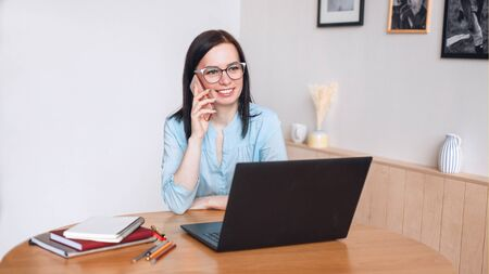 Businesswoman in conversation over phone and work at home office