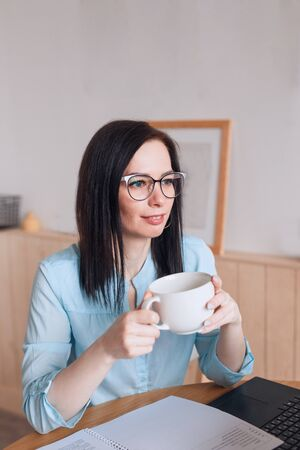 Smiliing woman drinking coffee while working online from home office