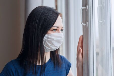 quarantined woman with covid-19 wearing a face mask looking at window