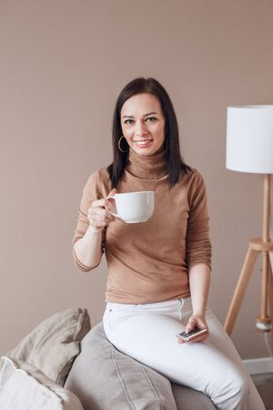 Beautiful woman at home drinking a cup of coffee and texting on her phone indoor Foto de archivo