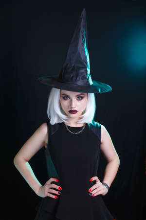 Beautiful young woman with white wig posing in witches costume. Happy Halloween