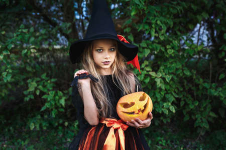 Little girl in witch costume on Halloween trick or treat in garden