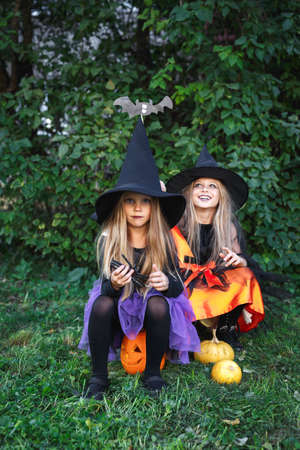 Funny girls in witch costume for Halloween sitting on pumpkin Jack outdoor