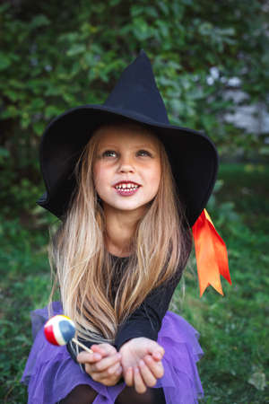 Funny little girl in witch costume eating Halloween candy outdoor 免版税图像