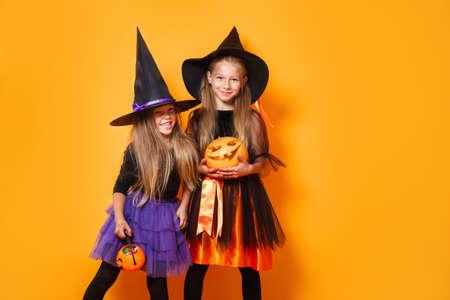 Two little girls in halloween costumes having fun on orange background 免版税图像