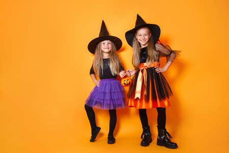 Happy child girls in witch costumes on orange background