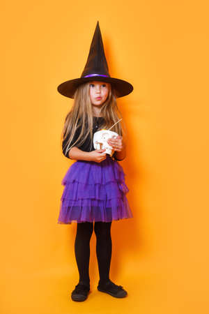 Laughing funny child girl in a witch costume in halloween on orange background
