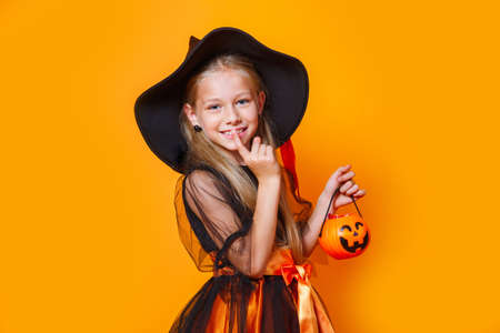 Little girl dressed as a witch and holding a pumpkin basket on orange background