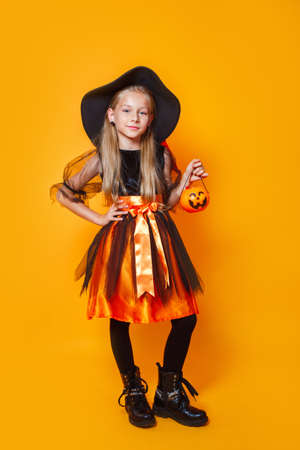 Little girl dressed as a witch and holding a pumpkin basket 免版税图像