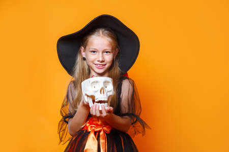 Cute little girl in witch Halloween costume on orange background
