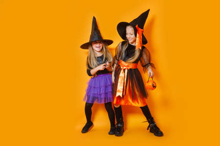 Laughing children in witches costumes on orange background