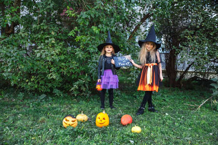 Halloween little girls in witch costume out for trick-or-treating