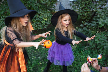 Little children trick or treating. Two little witches scare the neighborson on Halloween