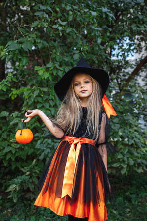 Funny child girl in witch costume for Halloween with pumpkin Jack outdoor 免版税图像
