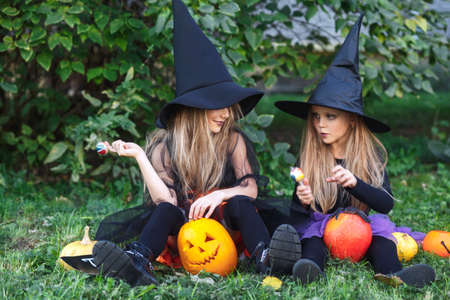 Two funny little sisters in witch costumes with Halloween candy and pumpkins outdoor 免版税图像