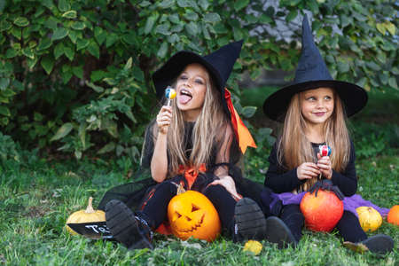 Two funny little girls in witch costumes eating Halloween candy