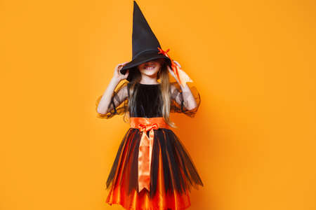 Portrait of a funny little girl dressed up as halloween witch on orange background