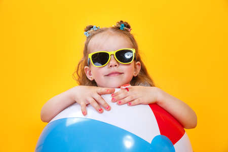 Summer girl wearing sunglasses with ball laughing on yellow background Imagens