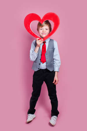 Valentines day. Smiling stylish little boy posing with heart on pink background
