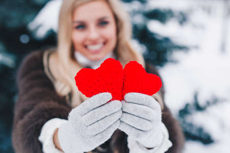 Two red knitting hearts in womens hands. Valentines day