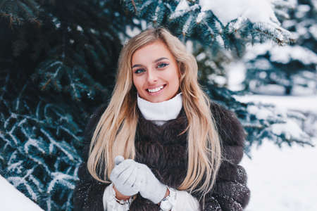 Close-up winter portrait of young woman with blond hair in forest