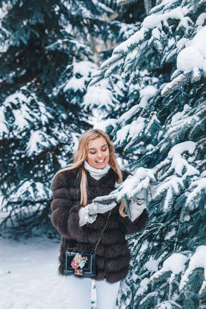 Beautiful young woman standing in winter snowy forest. Winter holidays concept