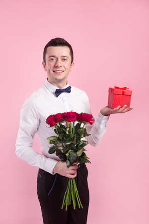 Valentines day. Handsome smiing boy holding flowers and gift box on pink background.