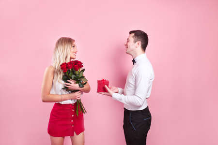 Valentines day. Handsome elegant boy is proposing to his beautiful girlfriend with her roses and smiling.