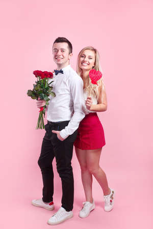 Happy Saint Valentines Day. Beautiful romantic couple with flowers and red heart on pink background.