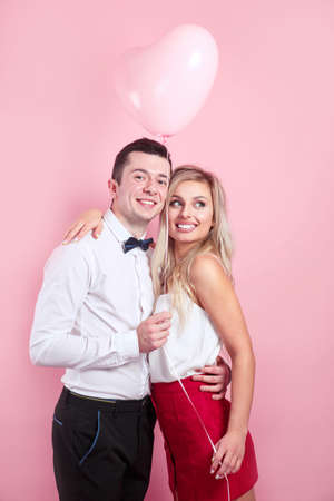 Valentines day. Beautiful romantic couple with heart balloon on pink background
