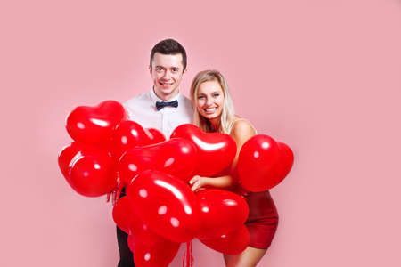Valentines day. Happy young couple with heart shaped balloons on pink background.