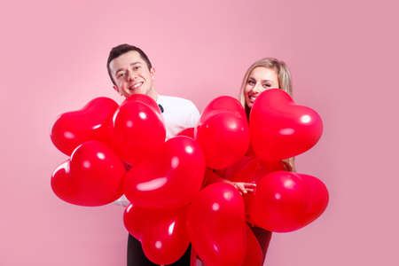 Valentines day. Surprised young couple with balloons heart on pink background 免版税图像