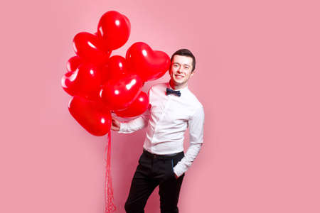 Happy Valentines Day. Elegant young man with heart shape air balloons on pink background. 免版税图像