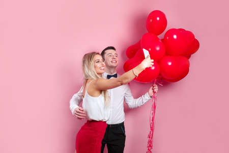 Valentines day. Romantic couple taking selfie on mobile phone and standing with red balloons on pink background 免版税图像