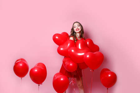 Happy Valentines Day. Beauty girl with red hearts balloons laughing on pink background