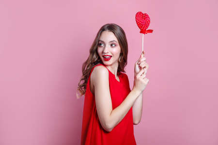 Beautiful brunette woman in red dress holding a red heart-shaped lollipop on pink background. Valentines Day