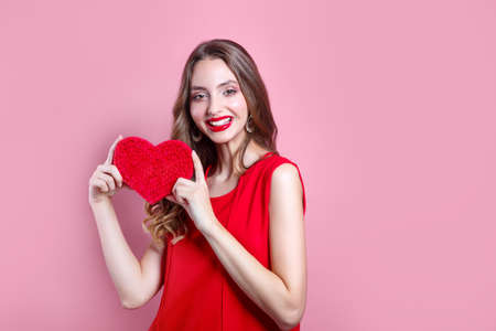 Valentines day. Beautiful girl with red lips holding artificial red heart on pink background 免版税图像