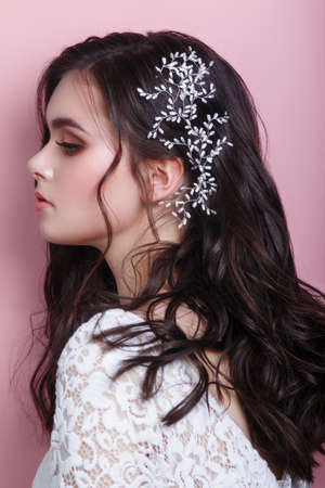 Portrait of beautiful woman wedding model with jewelry on hair looking away on pink background