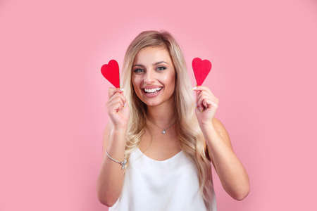 Valentines day. Beautiful smiling girl holding red hearts on pink background 免版税图像