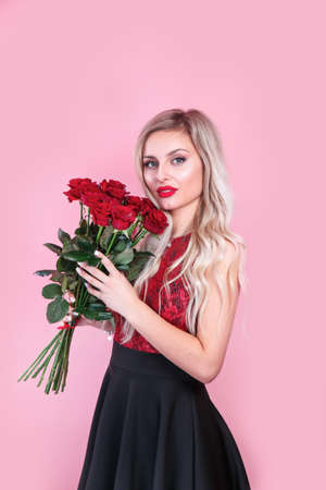 Portrait of a satisfied young woman in red dress holding bouquet of roses over pink background. Valentines day