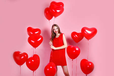 Valentines Day. Beautiful elegant young woman in red dress with heart shape red air balloons on pink background.