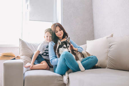 Mother, son and the husky dog sitting on sofa at home 免版税图像