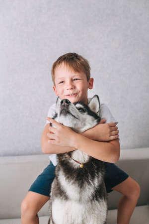 Happy little boy hugging husky dog at home