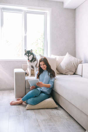 young woman sitting on the floor with her dog using tablet for work 免版税图像