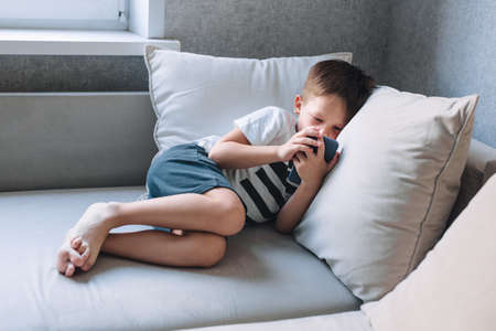 little boy lying on sofa and playing on phone at home 免版税图像