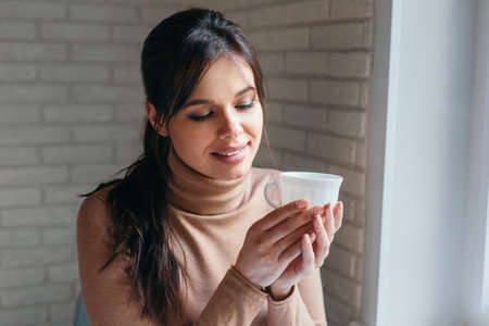 Woman drinking coffee or tea enjoying freetime in home office