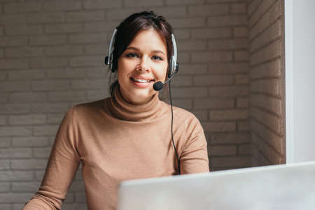 Smiling young woman call center operator with headset using computer at office