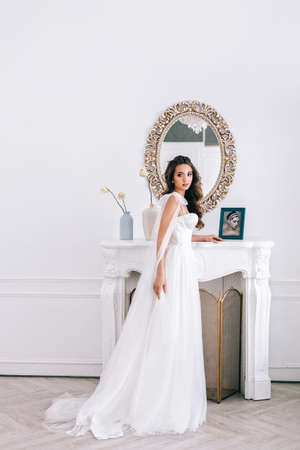 Glamorous young bride in wedding dress standing in studio