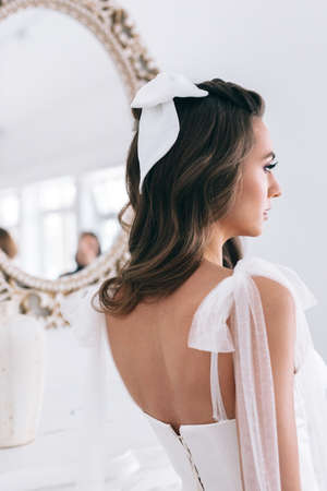Close-up of beautiful stylish bride with an elegant hairstyle view from the back . Studio shot