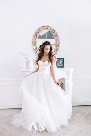 Beautiful woman wearing white dress in studio